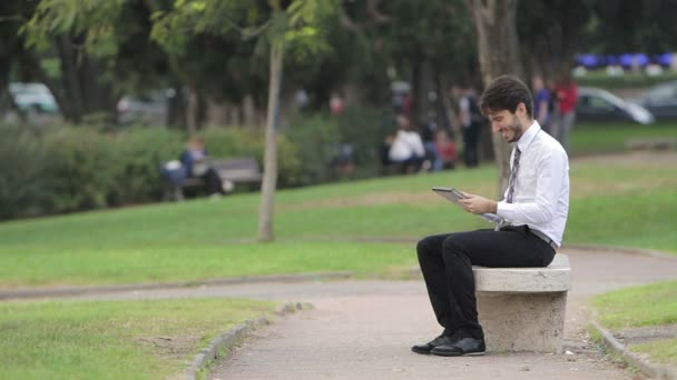Happy business man using tablet PC outside on a park