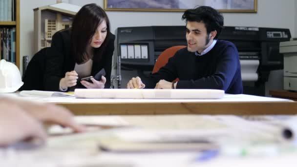 architect teamwork: designers working on blueprints