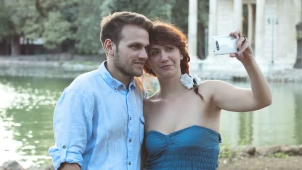 young couple in love making photos near the small lake; selfie, smartphone