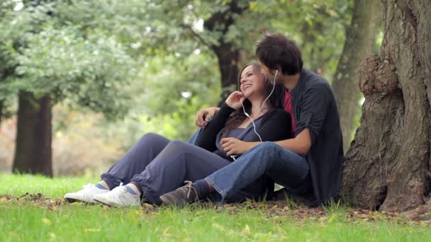 Loving young couple listening to the music in headphones on picnic together