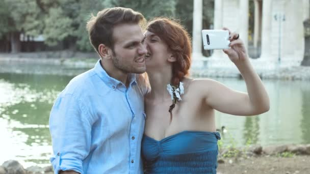 young couple having fun making photos near the small lake; selfie, smartphone