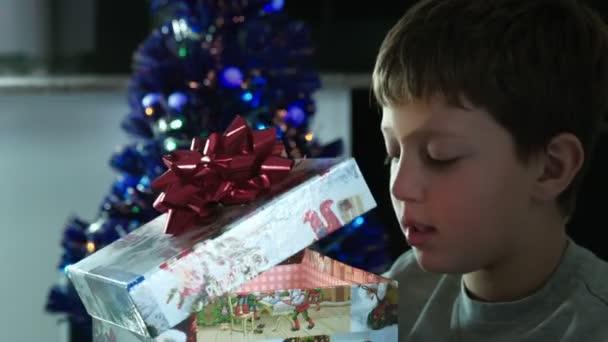 glückliches Kind öffnet ein Weihnachtsgeschenk mit einer schönen Schachtel Licht emittierenden