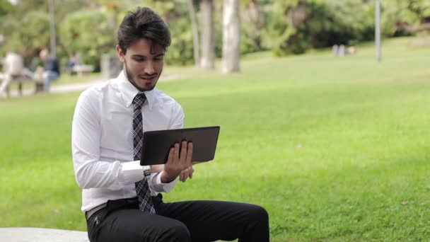 Young businessman at the park working with tablet