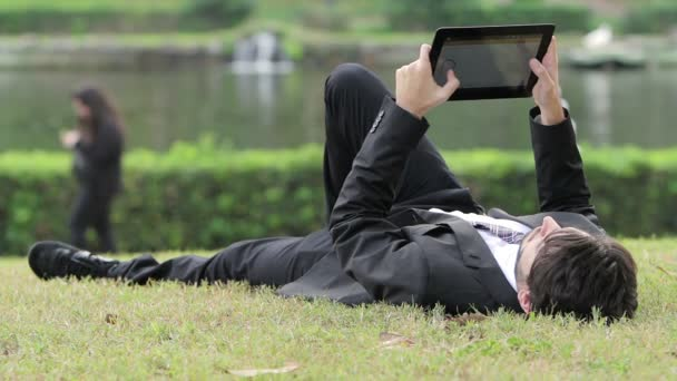 Businessman working outdoors with digital tablet PC at the park.