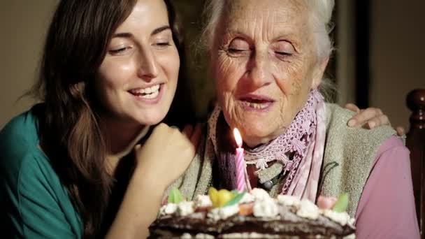 Happy smiling grandmother celebrating and giving a birthday cake to her grandson