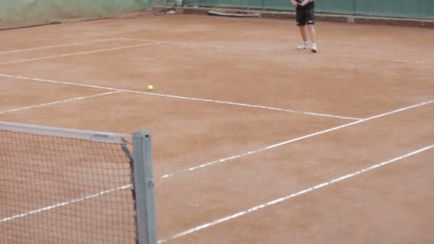 Muž hraje tenis na hřišti