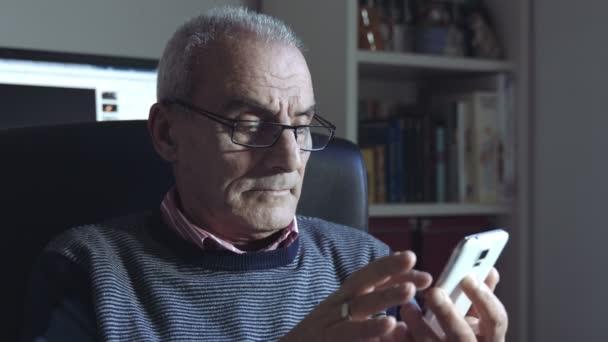 zamyšlený starý muž používá smartphone s dotykovým displejem