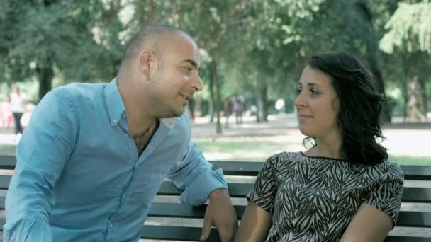 lidé, flirtování sedí na lavičce ve veřejném parku: úsměv a smích