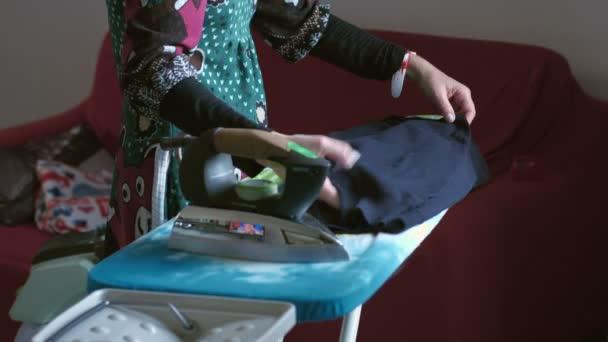 Hausfrau bügelt Kleidung