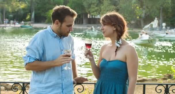 Young couple in love drinking red whine near a small lake: date, loving,