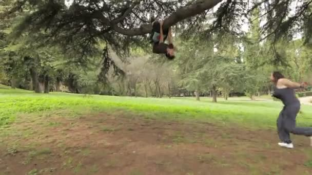 woman runs to her boyfriend and kisses him, the man is on the tree upside down