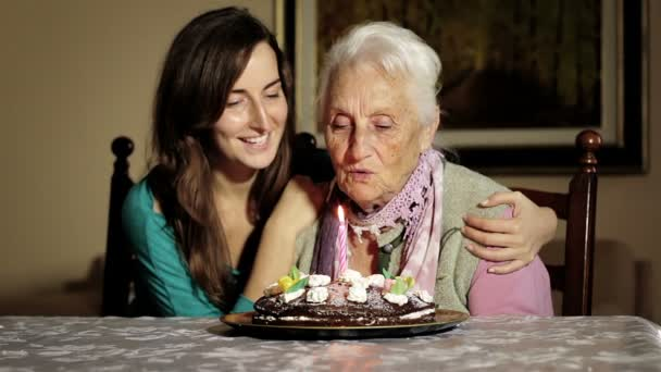 Old and young woman blow out her birthday candles.
