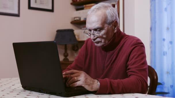 Alter Mann mit Laptop-Computer zu Hause arbeiten