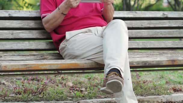 Freundlicher alter Mann mit Tablet-Computer im Park