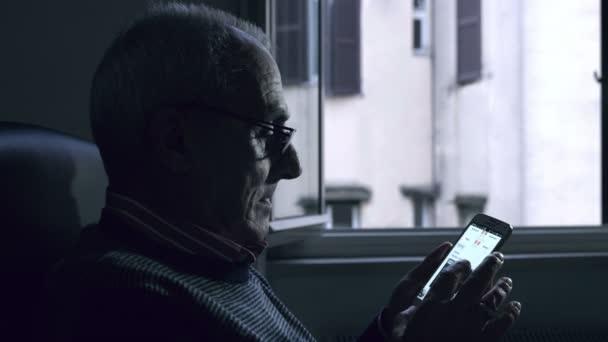 Starý muž pomocí smartphonu chce vidět zápasy fotbalové výsledky