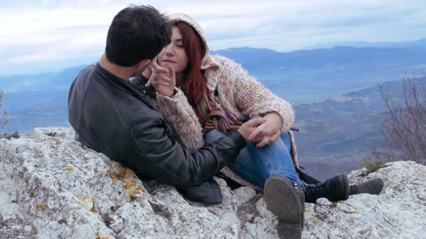 Young couple cuddling and kissing on the top of a mountain, excursion, love