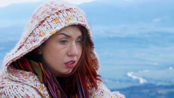 Woman in a hoodie, mountain track, windy day, hair, piercing, close up