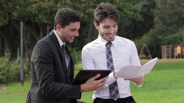 zwei glückliche Geschäftsleute mit Tablet-Computer sprechen über ein Projekt im Park