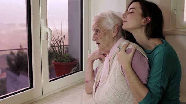 Grandmother and granddaughter embracing near windows