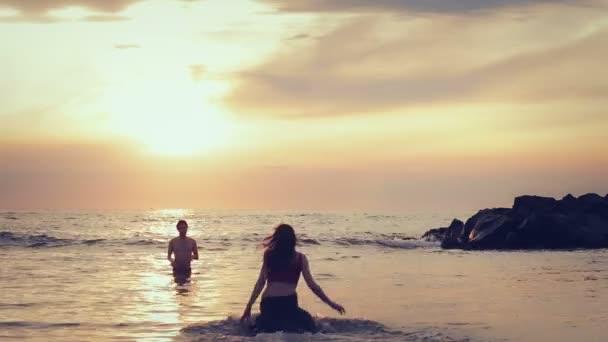 oblečená žena v lásce vede do svého muže do moře - objetí a polibky - západ slunce