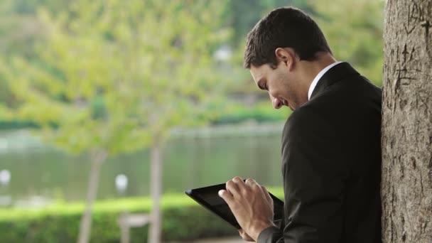 Obchodní muž pomocí digitálních tabletu v parku