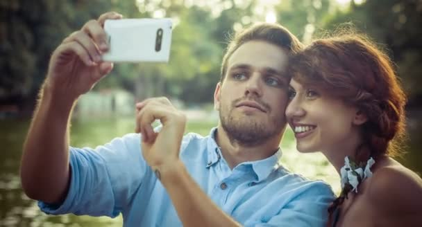 young couple in love makes selfie in a public park: smart phone, photo