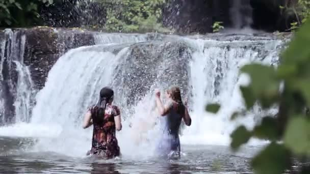 girls of boys have fun in a river - dancing, hugging and playing with water