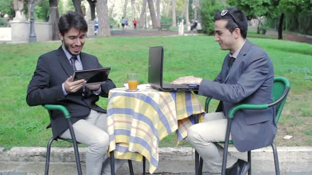 Two businessmen using tablet and laptop during an informal meeting in a bar