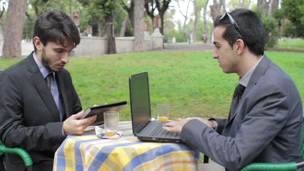 Podnikatelé s digitálním tabletu a notebooku během neformální setkání