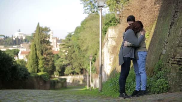 pohledný mladý pár líbání v krásném parku