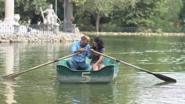 couple kissing on the rowboat: lovers having  romantic moment on the lake