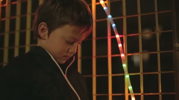 child plays with the colored lights of christmas decoration