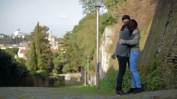 Fiatal pár csók az utcán egy régi fal mellett