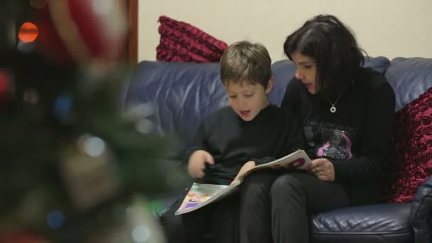 Mom and young son reading a book of fairy tales - during the Christmas season