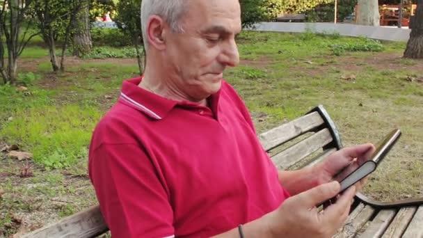 ehemaliger leitender Mann ruht und mit seinem Tablet am Tisch im park