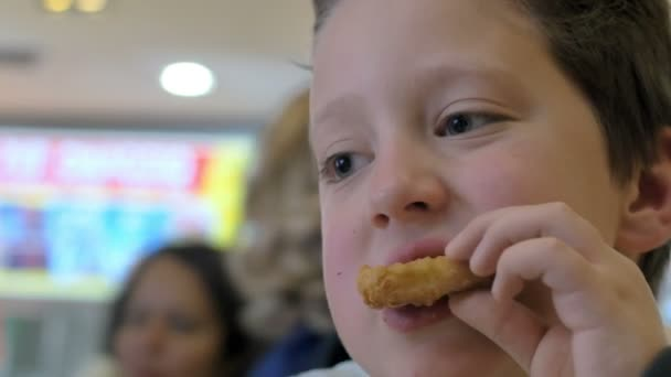 Child eating fried chicken in a fast food restaurant: junk food