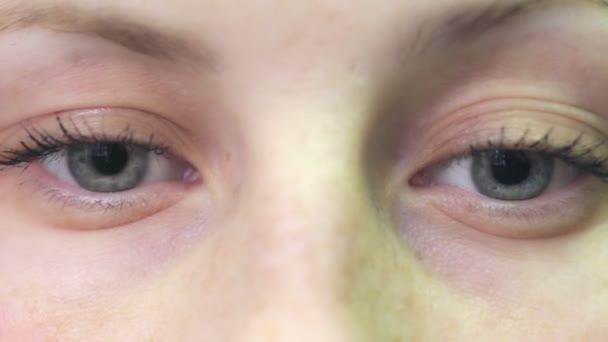 krásná žena se dívá do kamery a ukazuje své modré oči