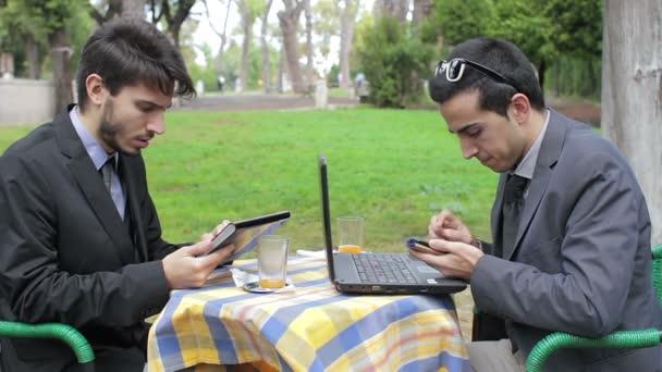 Két üzletember tabletta és laptop használata során informális ülést egy bárban
