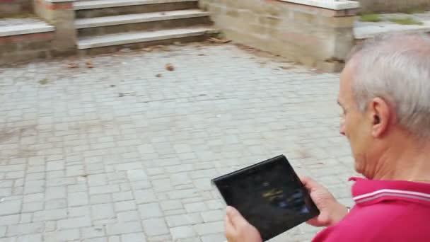 Alter Mann mit Tablet im Park entspannen