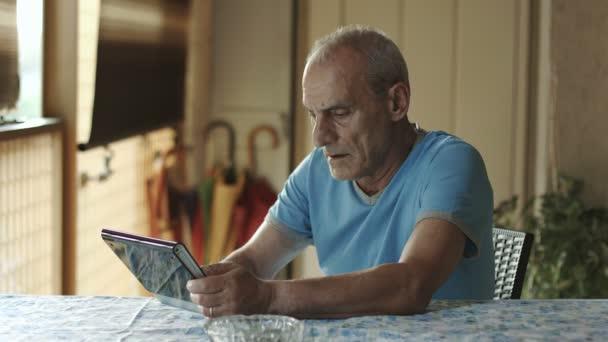 Alter Mann nutzt Tablet-Computer zu Hause: ältere Menschen, Technik, Internet