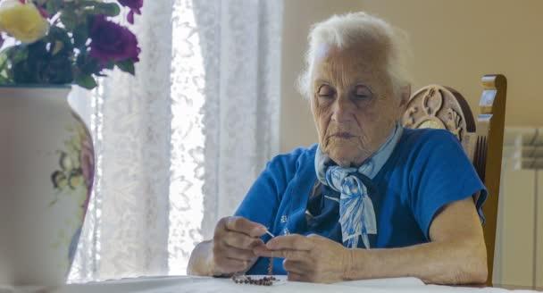 Idős asszony imádkozik a rózsafüzért gyöngyök, megfeszített Krisztus, kereszt, régi