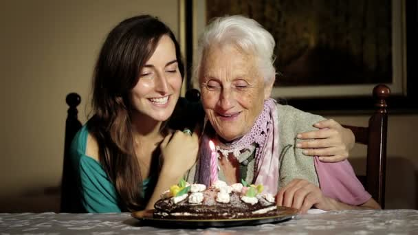 An young happy woman and his grandmother blow out her birthday candles