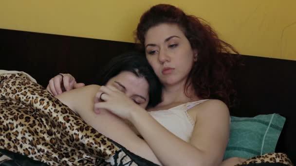 Egy fiatal lány hugs a másik lány az ágyban, és teszi a megcirógatja neki