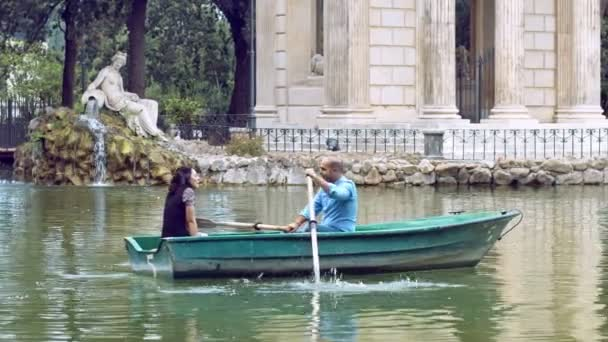 people having a romantic tour on rowboat in villa Borghese in Rome