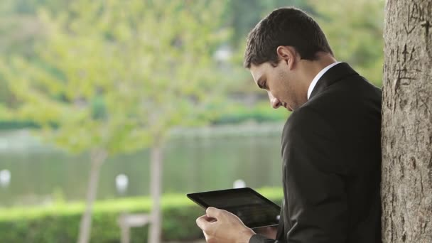 Happy business young man using tablet PC outside on a park