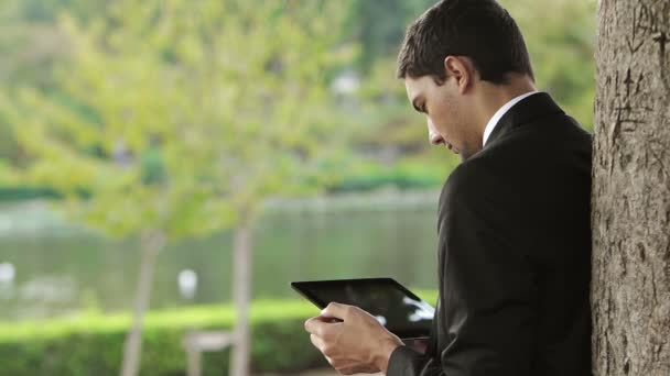 Young Businessman using tablet PC outside on a park