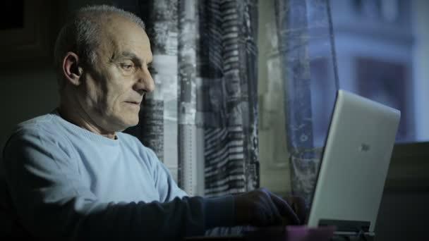 Alter Mann arbeitet spät in der Nacht am Computer, während er eine Zigarette raucht
