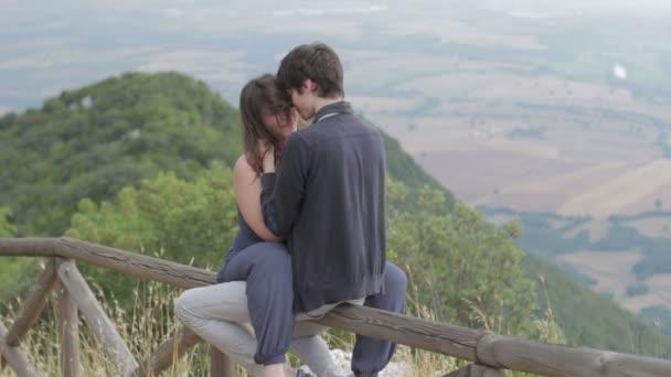 milující pár líbání, sedí na plotě v horách, pohladí