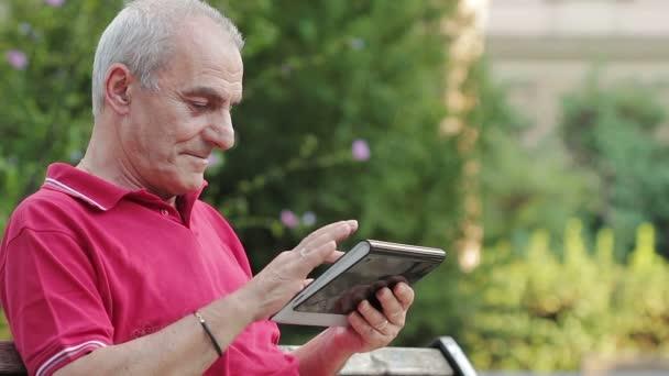 Freundliche gut aussehend Greis mit Tablet-Computer im park