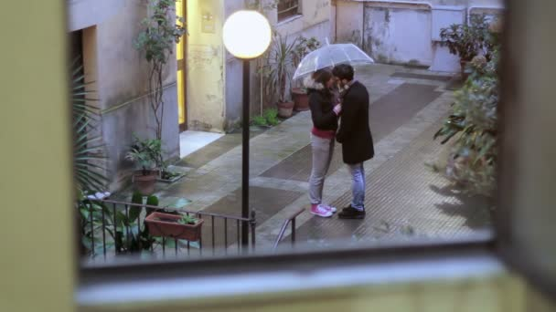 young man and a woman kissing under an umbrella in the rain